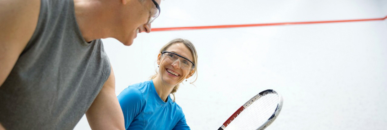 Couple in goggles playing squash